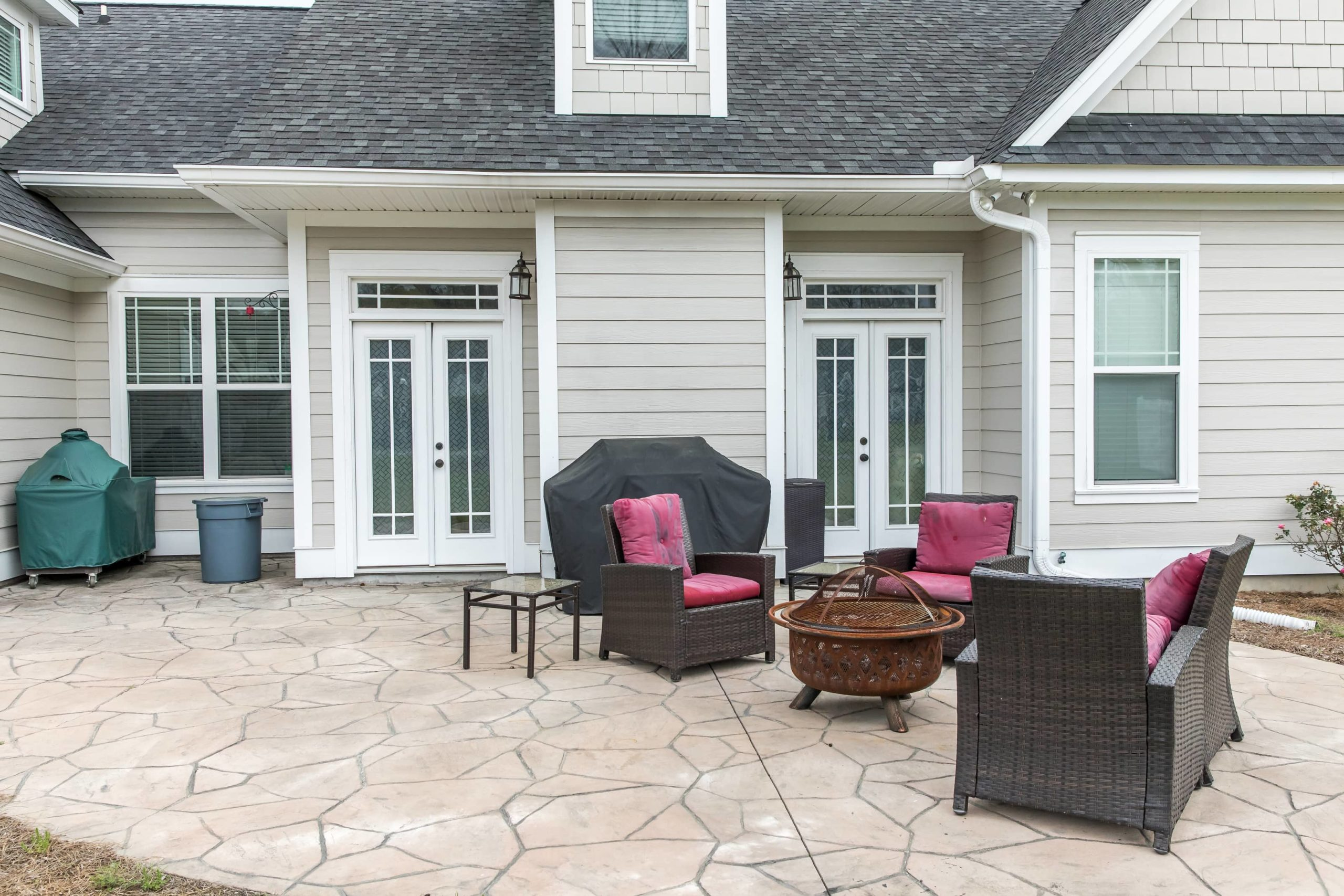 This is an image of a cozy concrete patio with sofas and firepit.