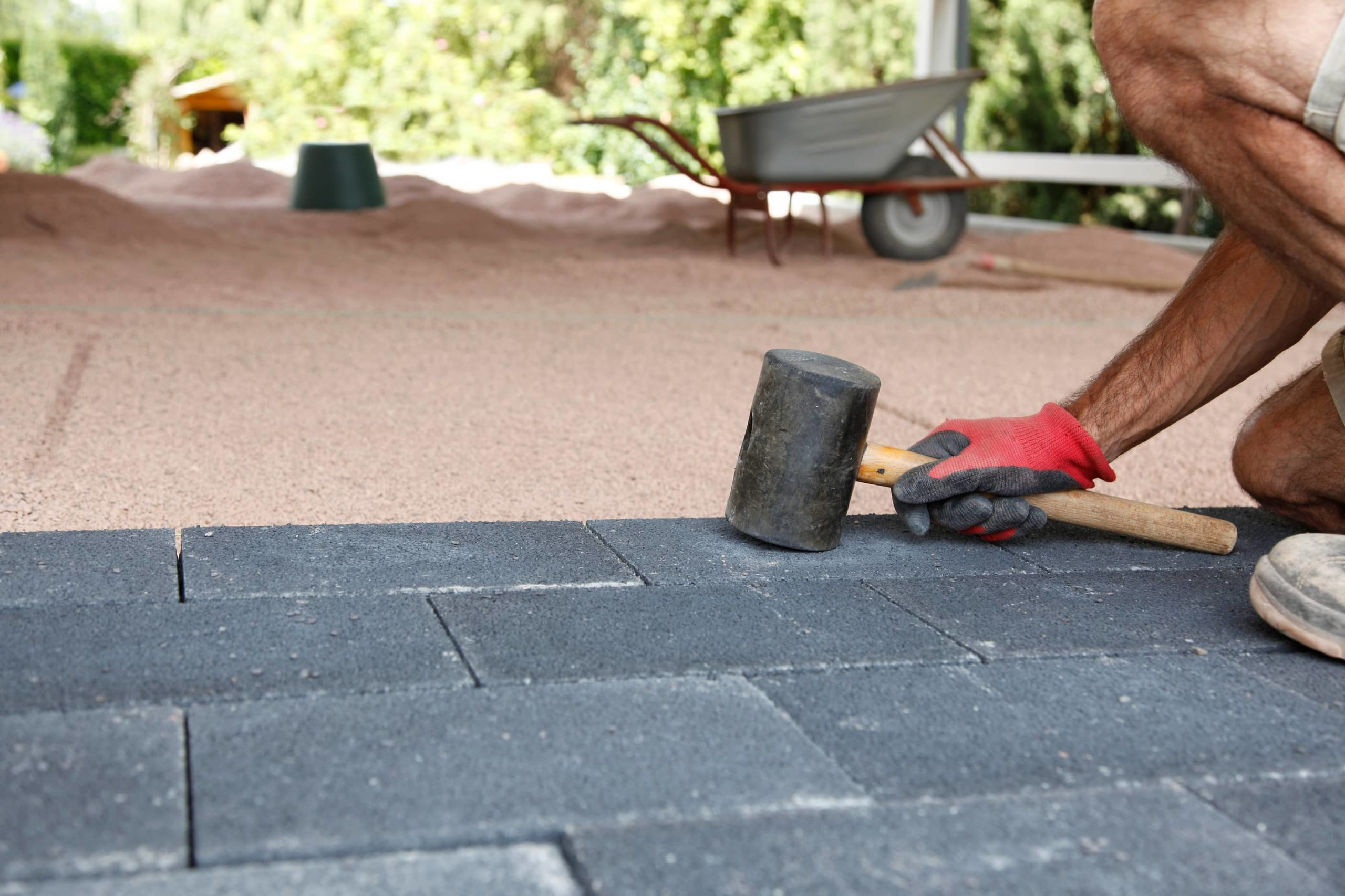 This is an image of a contractor laying concrete paving bricks.