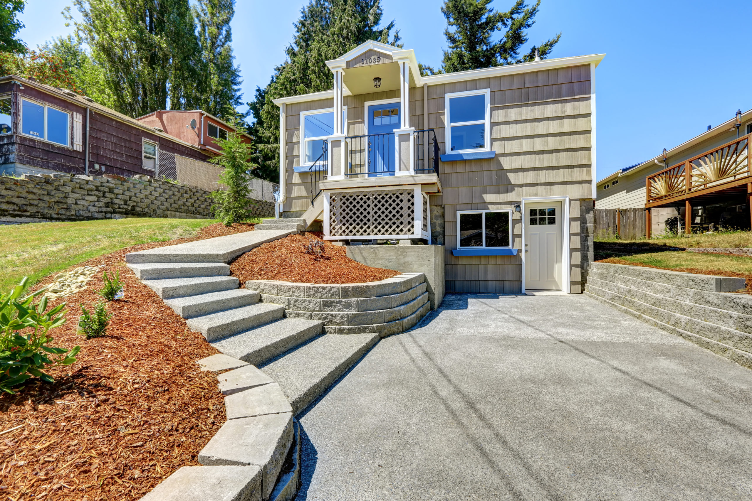 This is an image of a residential property with a concrete driveway and stairs.