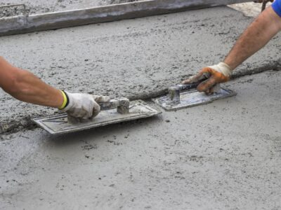 This is an image of two contractors smoothing out wet concrete with trowels.